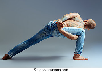 yoga posture - A man doing yoga exercises. Studio shot over...