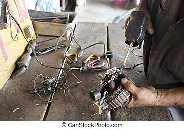 Old man 60 year old thai people professional automotive motor mechanic lead-free solder for repair