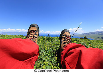 hiker sitting on a grass mountain top with first person...