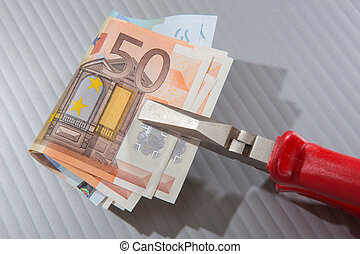 euro banknotes clamped in flat-nose pliers close up