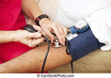Testing Blood Pressure - Closeup - Nurse taking a patients...