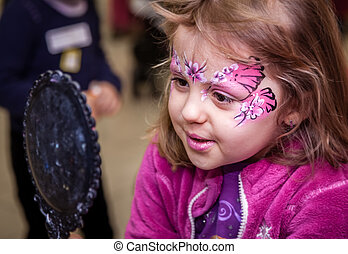 Admiring face paint - Little girl having her face painted...