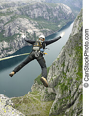 rope jumping - Jump off a cliff into a canyon with a rope.