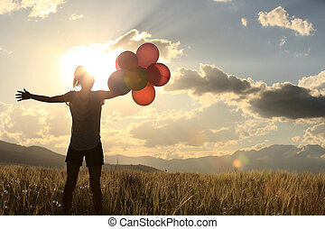 cheering young asian woman on sunset grassland with colored...