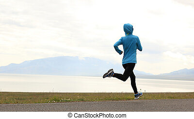 healthy lifestyle young woman runner running on seaside...