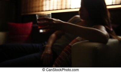 sad lonely woman drinks alcohol in the dark. Glass in sharp...