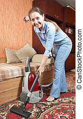 Friendly Maid Vacuuming - Photo of an attractive senior...