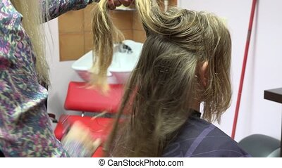Barber hands comb blond female customer hair at hairdressers...