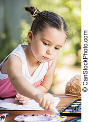 Little girl painting outdoor