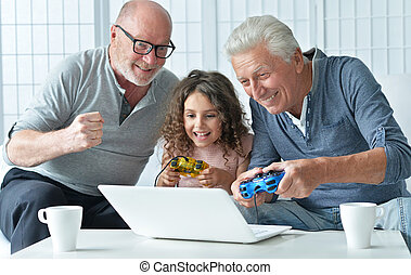 senior men and granddaughter with laptop