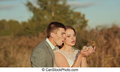 The bride and groom break dandelion fluff. - The bride and...