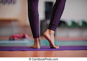 woman standing at yoga class - woman standing barefoot at...