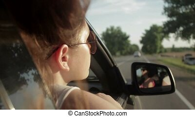 Wind Blowing Through Girl's Hair In a car. Sunset....