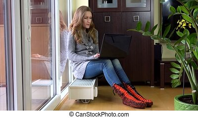 Cute woman have fun with laptop sitting on warm radiator at...