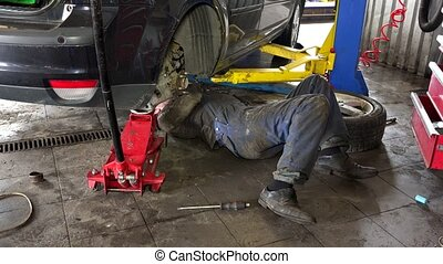 Mechanic lying and working under car at repair garage -...
