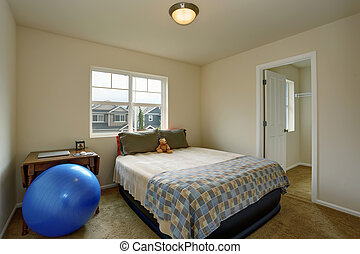 Small kids bedroom with table, blue ball and small green bed