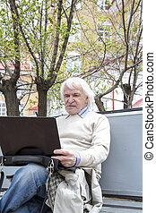 Senior man using laptop computer outdoors - Senior man using...