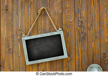 blank space on black chalk board with rope on wooden door of...