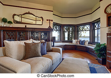 Vintage style living room with beige sofa and antique wooden cabinet.
