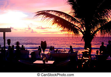 Restaurant by the beach during sunset with palm tree
