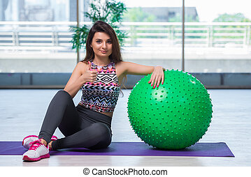 Young woman exercising with swiss ball in health concept