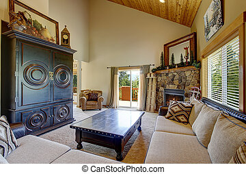 Cozy living room with high wooden vaulted ceiling and carpet...
