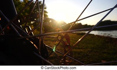 Close up shot of a rotating disc brake of a bike against sun...