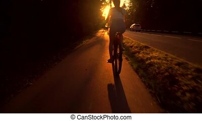 Slim brunette girl riding a bike along summer sunset road....
