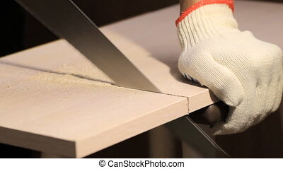 Man sawing wooden board with hand saw, indoors