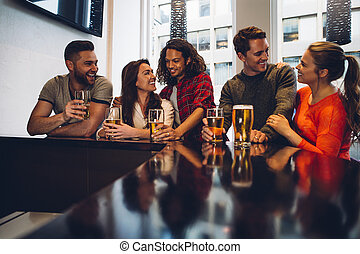 Friends in a Bar - Group of friends enjoying a beer at a...