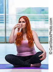 Woman drinking fresh water in gym