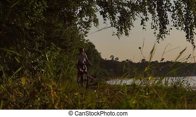 Slender brunette girl riding a bike along summer riverside. Slow motion shot