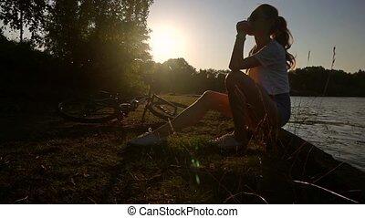 Slim brunette girl biker relaximg in the sun. Slow motion...