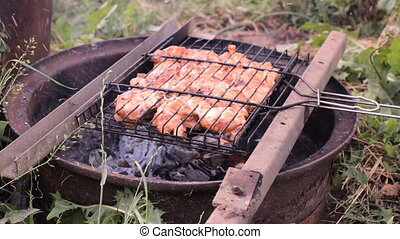 Chicken meat pieces being fried on a charcoal grill -...