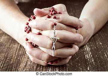 Hands praying with cross