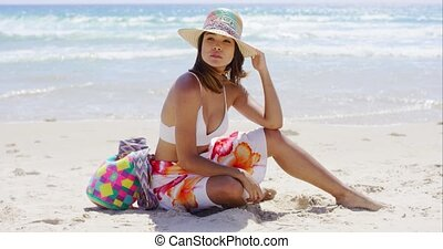 Pretty young woman sitting on the beach sand