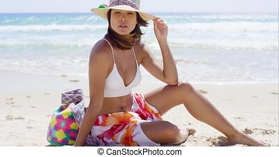 Pretty young woman sitting on the beach sand at the edge of...