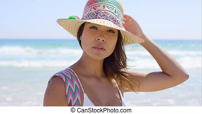 Smiling young woman holding her sunhat in the sea breeze as...
