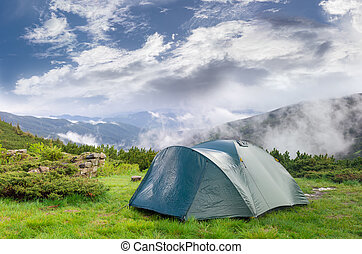 Hiking tent after rain on background of mountains and sky -...
