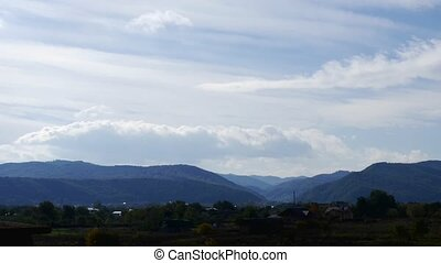 TIme lapse. clouds pass over above the village in the mountains.