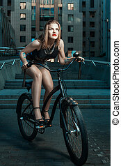 Girl in a rock style. - Girl in a rock style rides a bicycle...