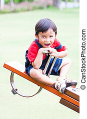 Boy smiling and play at the see-saw in the playground
