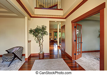 Hallway in creamy colors with polished hardwood floor and brown trim.