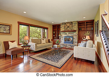 Family room in antique style with natural stone design fireplace and old sofa set.