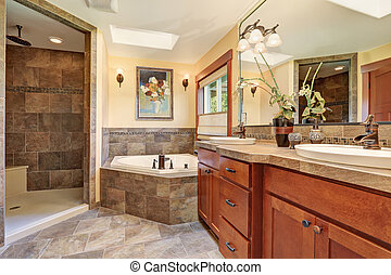 Lovely master bathroom with stone floor and large...