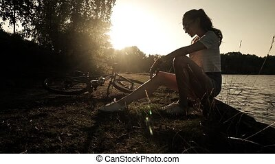Slender girl cyclist with ponytail hairstyle having a rest. Slow motion shot against sunset