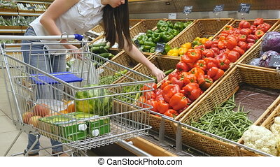 Young woman pushing cart along the grocery aisles in the supermarket.