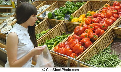 Young pretty girl is choosing peppers in a grocery supermarket. Attractive woman selecting fresh ripe red peppers in grocery store produce department.