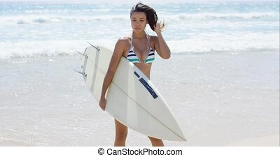Sexy pretty young woman surfer carrying her surfboard along...
