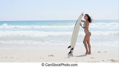 Beautiful young sunbathing woman holding surfboard near the...